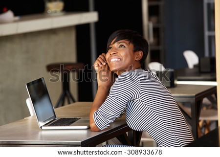 Side portrait of a cheerful young woman sitting at cafe with laptop - stock photo