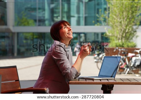 Side portrait of a happy business woman laughing with cup of tea and laptop at outdoor cafe - stock photo