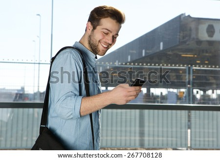 Side portrait of a happy modern man sending text message at airport - stock photo