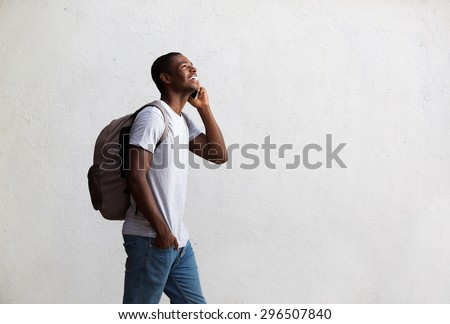 Side portrait of a happy student walking and talking on mobile phone - stock photo