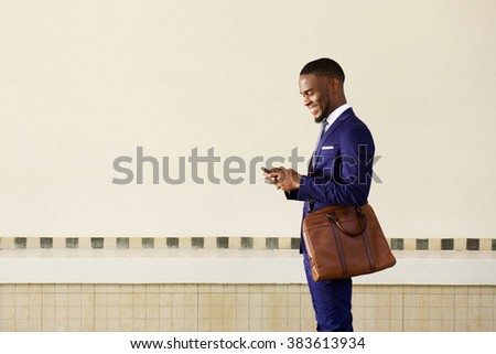 Side portrait of a happy young businessman with bag  reading text message on mobile phone  - stock photo