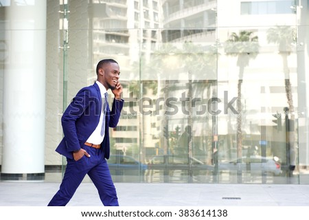 Side portrait of a happy young man in suit walking and talking on mobile phone  - stock photo