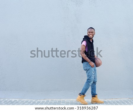 Side portrait of a happy young man walking on sidewalk with basketball