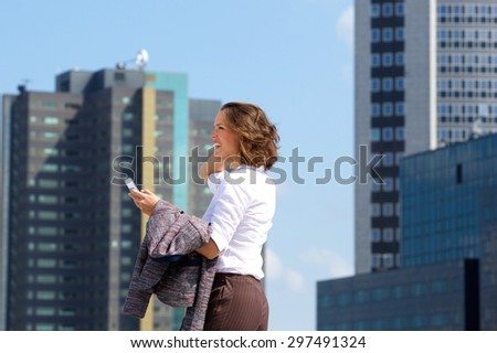 Side portrait of a smiling business woman walking in the city with mobile phone - stock photo