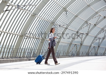 Side portrait of a smiling business woman walking with bag at station - stock photo