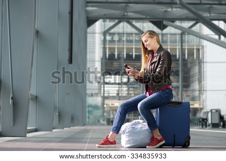 Side portrait of a smiling young woman sitting on suitcase and looking at mobile phone