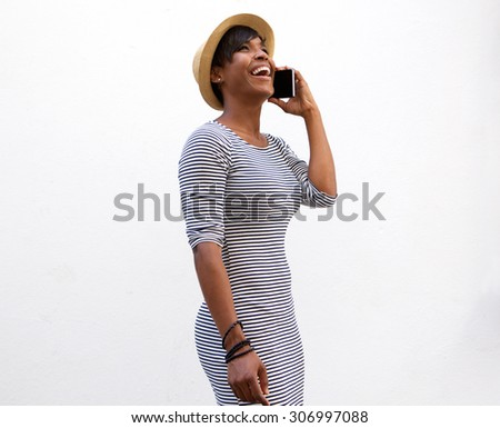 Side portrait of a smiling young woman walking and talking on cell phone - stock photo
