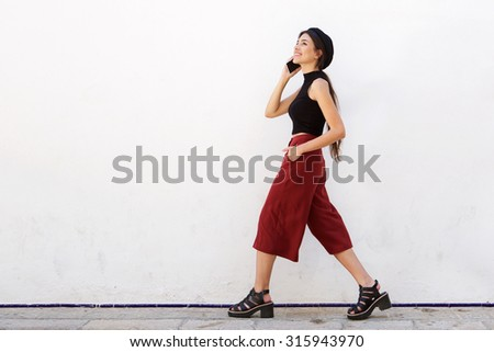 Side portrait of a smiling young woman walking with mobile phone - stock photo
