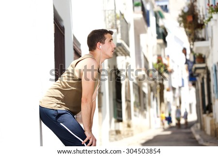 Side portrait of a tired man resting after workout - stock photo