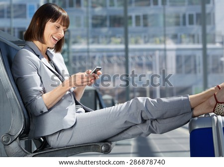 Side portrait of a traveling business woman smiling with mobile phone - stock photo