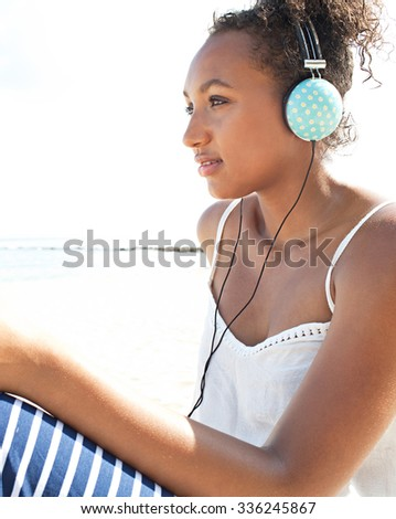 Side portrait of a young african american teenager sitting by the sea on the beach, using headphones to listen to music, smiling relaxing on a sunny holiday, outdoors. Technology and travel lifestyle.