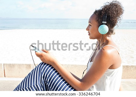 Side portrait of a young african american teenager sitting by the sea on the beach, using a smartphone and headphones to listen to music on a sunny holiday, outdoors. Technology and travel lifestyle. - stock photo