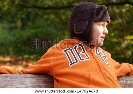 Side portrait of a young boy sitting on a wooden bench in a park in the countryside during a winter day, wearing a warm hat and a jumper while relaxing outdoors.