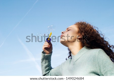 Side portrait of a young girl wearing a blue jumper and playing at blowing soap bubbles against a blue sky during a sunny winter day. - stock photo