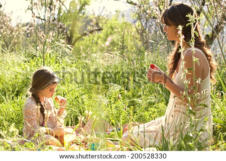 Side portrait of a young mother and daughter sitting together in a sunny field of grass and flowers having a picnic, enjoying a summer holiday. Eating and relaxing family activities lifestyle. - stock photo