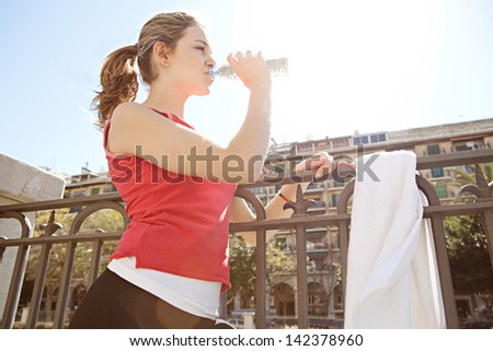 Side portrait of a young woman taking a break from exercising in the city, drinking from a blue plastic bottle of mineral water during a sunny morning run. - stock photo