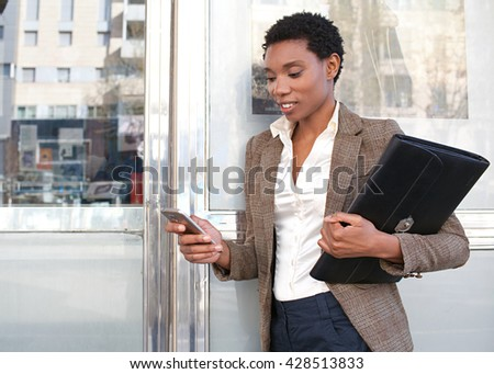 Side portrait of african american business woman leaning on reflective office building smiling outdoors, using smart phone to work, city exterior. Professional black woman using technology, exterior.