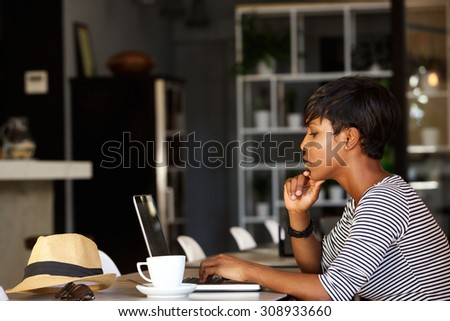 Side portrait of an african american woman using laptop at cafe restaurant - stock photo