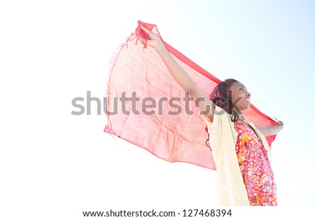 Side portrait of an attractive african-american woman holding a red fabric sarong up in the air against a bright blue sky while on vacation, smiling. - stock photo