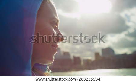 Side portrait of an attractive woman in a hood looking out to the city over a river on a sunny day, with sun flare - stock photo