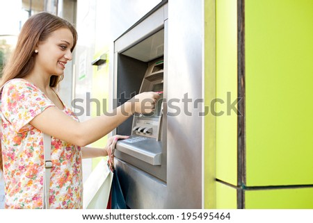 Side portrait of an attractive young woman using a cash point machine with her credit card to withdraw money while shopping in a city and carrying paper bags. Consumerism and lifestyle, outdoors. - stock photo