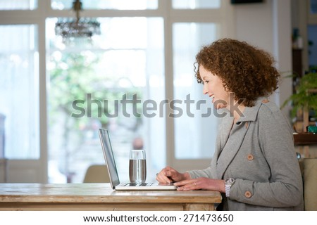 Side portrait of an older woman smiling and using laptop at home - stock photo