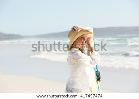 Side portrait of attractive young caucasian woman in hat with surfboard standing on the beach