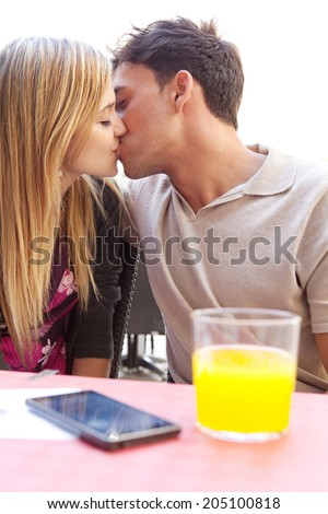 Side portrait of attractive young couple on holiday being romantic and holding their foreheads together while sitting at a coffee terrace bar drinking refreshments during a summer vacation, outdoors. - stock photo