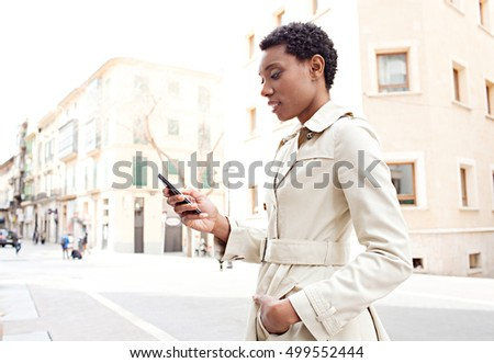 Side portrait of beautiful elegant african american professional woman holding and using a smart phone in classic city street, outdoors. Black businesswoman travel and technology lifestyle.