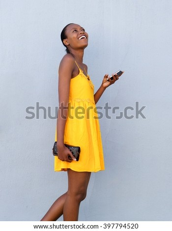 Side portrait of cheerful african woman walking with mobile phone against gray background - stock photo