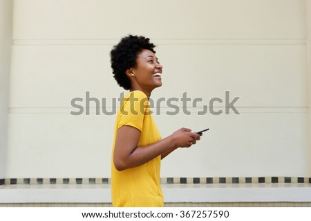 Side portrait of cheerful young african woman walking with a mobile phone - stock photo