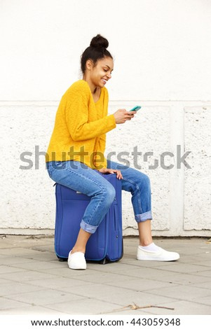 Side portrait of cheerful young woman using mobile phone and sitting on suitcase - stock photo