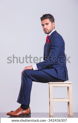 side portrait of man in business suit sitting in studio looking at the camera