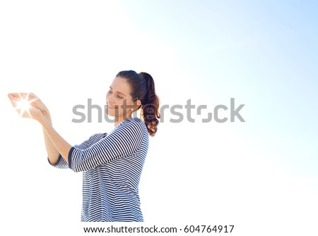 Side portrait of mature woman smiling, holding the sun in her hands against sky, outdoors. Space with sun rays and light filtering through, conceptual natural resources, nature caring and environment.