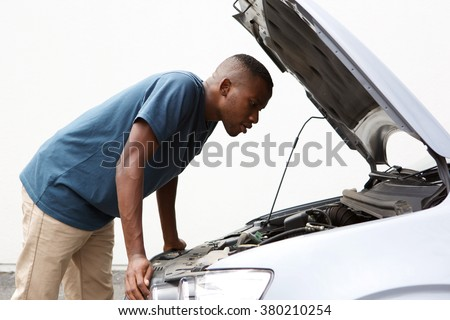 Side portrait of young african american guy looking under the hood of broken down car - stock photo