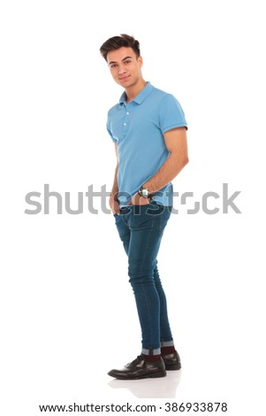 side portrait of young man walking with hands in pockets in isolated studio background while looking at the camera  - stock photo