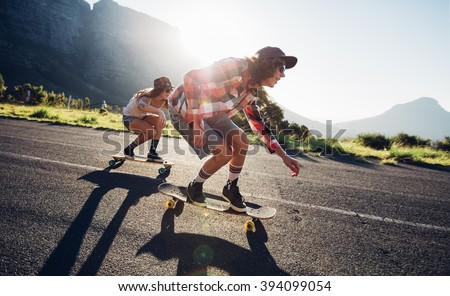 Side portrait of young people skateboarding together on road. Young man and woman longboarding down the road on a sunny day. - stock photo