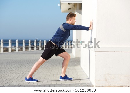 Side portrait of young sports man pushing against wall