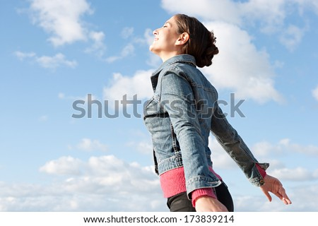 Side portrait view of a beautiful young woman on holiday by the sea, breathing fresh air on the coast against an intense blue sky during a sunny day. Outdoors lifestyle healthy beauty. - stock photo