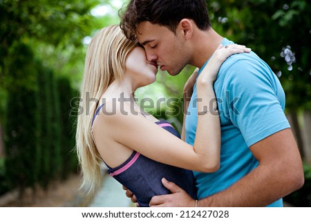 Side portrait view of a passionate romantic young couple kissing and embracing while in a green park on holiday. Young people romantic lifestyle and love, outdoors. - stock photo