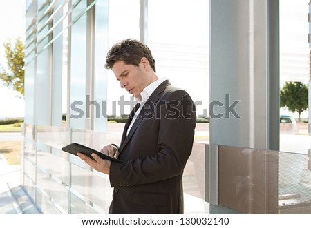 Side portrait view of a smart senior businessman using a technology tablet while leaning on a glass modern architecture office building in the city. - stock photo