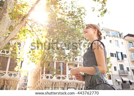 Side portrait view of young tourist woman contemplating sightseeing sunny destination city with direct light flare and classic buildings, exterior. Professional woman in golden aspirational outdoors. - stock photo