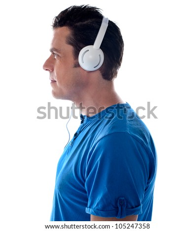 Side pose of a man with headphones. Tuned into music - stock photo