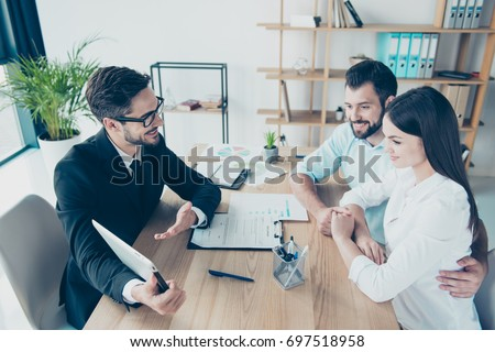 Side profile high angle shot of a deal between married couple and a salesman, consultating them about buying a purchase, all are dressed in formal outfits, smiling