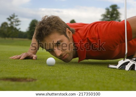 Side profile of a mid adult man judging a golf ball in a golf course - stock photo