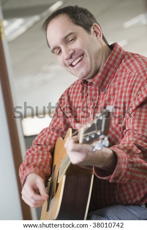 Side profile of a mid adult man playing a guitar - stock photo