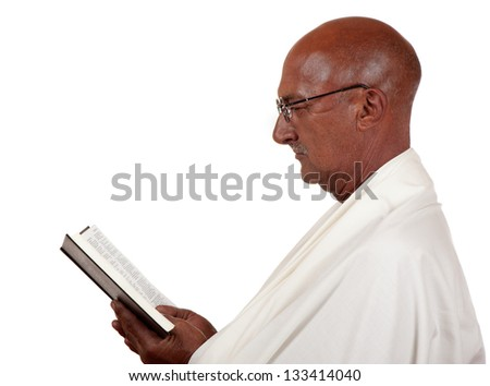 Side profile of a senior man concentrating heavily on a holy book he is reading.