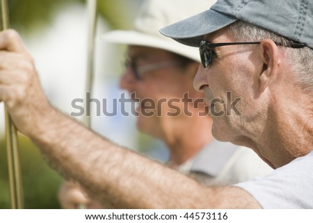 Side profile of a senior man holding a shuffleboard cue - stock photo