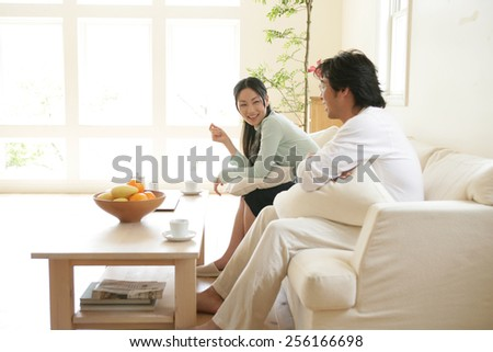 Side profile of a young couple sitting on a couch and smiling - stock photo