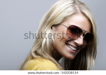 Side profile of an attractive and cheerful female model in sunglasses looking straight into camera, isolated on white background.